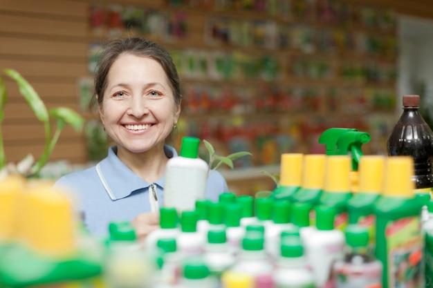Femme heureuse choisit un engrais liquide Photo gratuit
