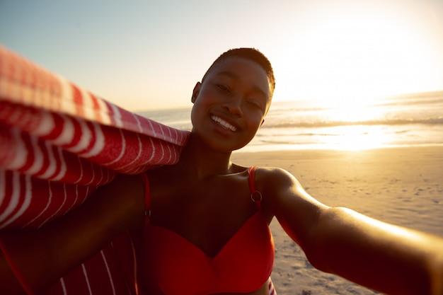 Femme heureuse avec couverture debout sur la plage Photo gratuit