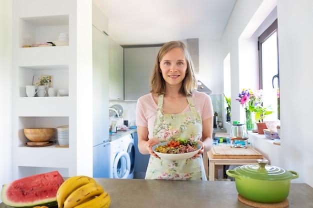 Femme Heureuse, Cuisiner à La Maison, Maintenir Une Alimentation Saine, Tenant Un Bol De Plat De Légumes Maison, Souriant à La Caméra. Vue De Face. Concept D'alimentation Saine Photo gratuit