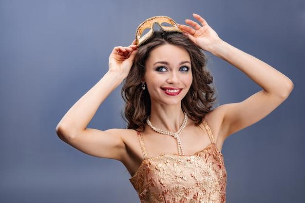 Femme heureuse dans une robe en or et un collier de perles portant un masque de carnaval sur la tête Photo Premium