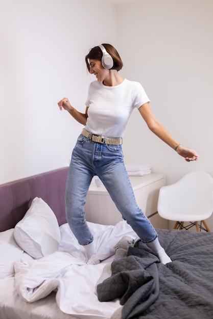 Femme Heureuse Dans Des Vêtements Décontractés à La Maison Dans La Chambre écoute De La Musique Dans Les écouteurs, Dansant Et Sautant Photo gratuit