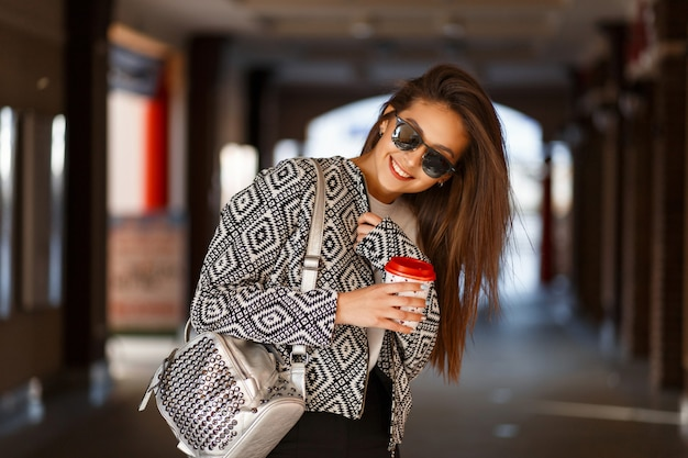 Femme Heureuse Avec Du Café Dans Des Vêtements De Mode Avec Un Sac Se Promène Dans La Ville Photo Premium