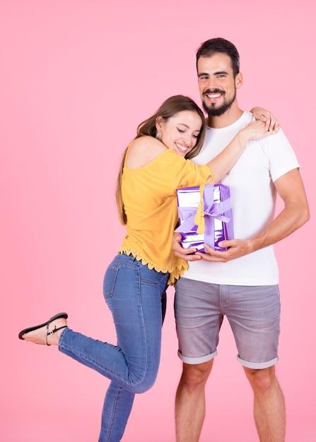 Femme heureuse, étreindre, à, elle, petit ami, tenue, emballé, cadeaux, sur, rose, toile de fond Photo gratuit