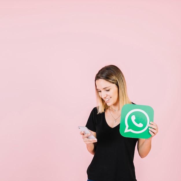 Femme heureuse avec l'icône de whatsapp à l'aide de téléphone portable Photo gratuit