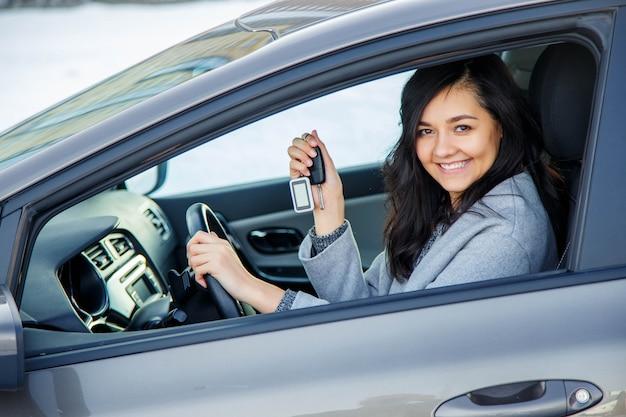 Femme heureuse montre les clés de la nouvelle voiture. Photo Premium