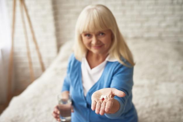 Femme heureuse montre des pilules dans la ménopause à la main. Photo Premium