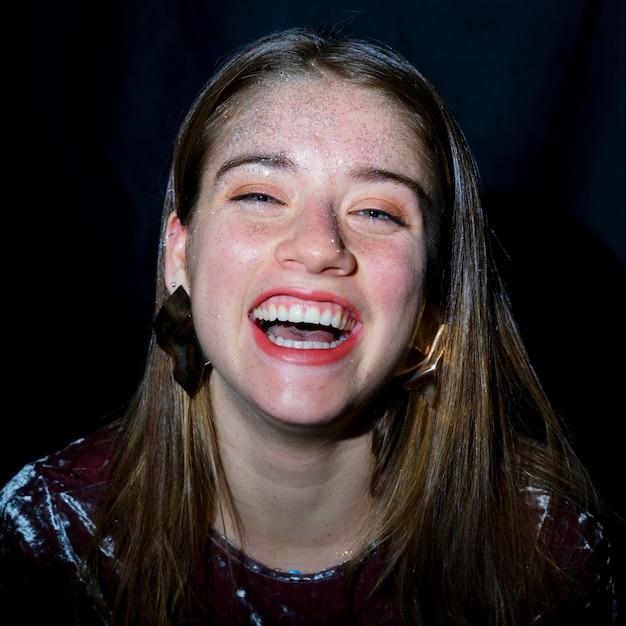 Femme heureuse avec paillettes sur le visage Photo gratuit