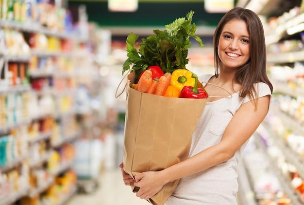 Femme heureuse positive en bonne santé tenant un sac en papier rempli de fruits et de légumes Photo Premium