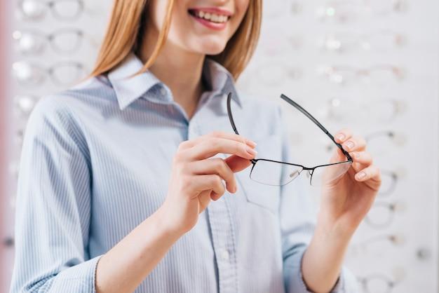 Femme heureuse à la recherche de nouvelles lunettes chez l'optométriste Photo gratuit