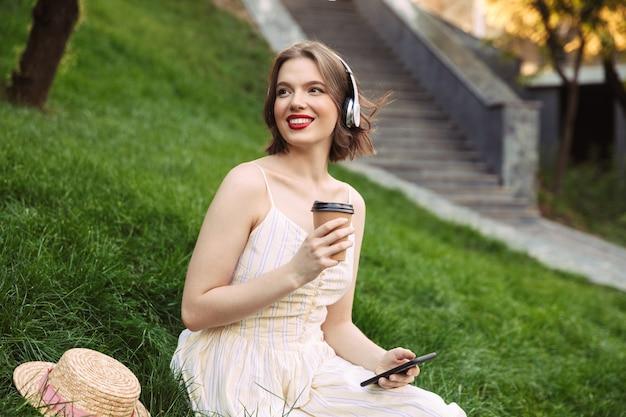 Femme Heureuse En Robe Et Casque, Boire Du Café Et écouter De La Musique Assis Dans Le Parc Photo Premium