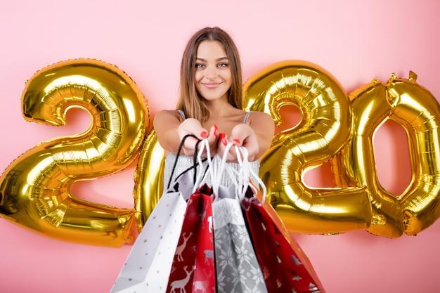Femme Heureuse Avec Des Sacs-cadeaux De Magasinage De Noël Avec Des Ballons Dorés De 2020 Isolés Sur Rose Photo Premium