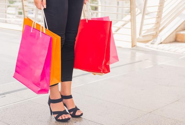 Femme heureuse avec des sacs à provisions bénéficiant d'achats. shopping femme, concept de mode de vie Photo Premium