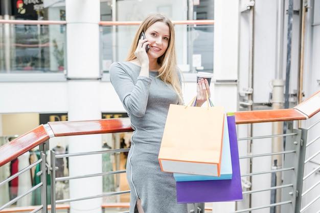Femme heureuse avec des sacs à provisions parlant sur téléphone mobile Photo gratuit