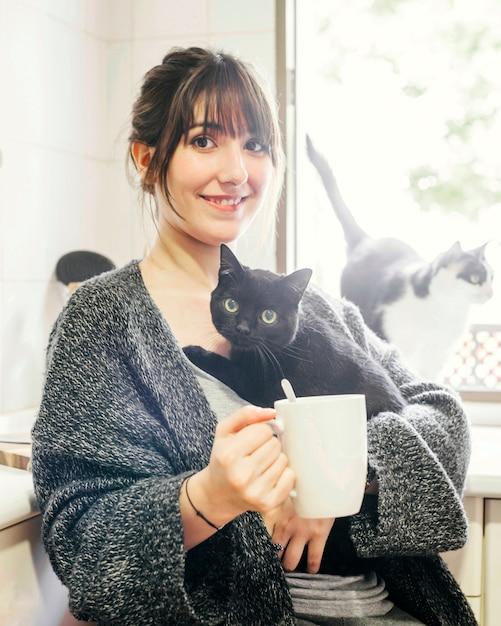 Femme heureuse avec une tasse de café tenant son chat Photo gratuit