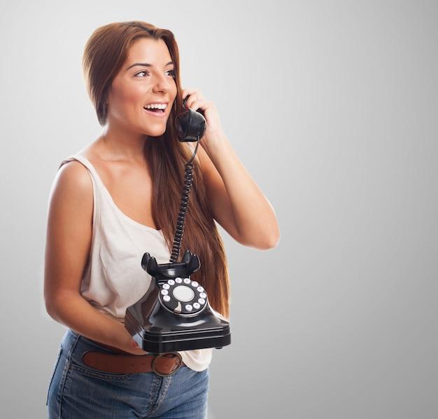 Femme heureuse avec téléphone fixe et le combiné Photo gratuit