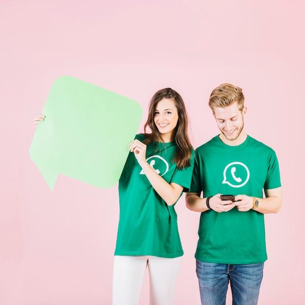 Femme heureuse tenant la bulle de dialogue à côté de l'homme à l'aide de smartphone Photo gratuit