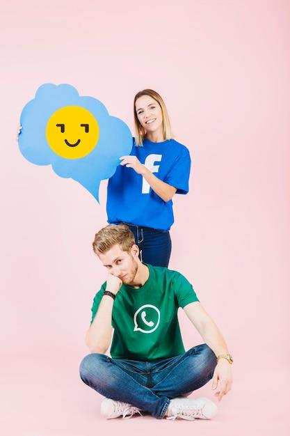 Femme heureuse tenant la bulle de pensée emoji derrière l'homme contrarié Photo gratuit