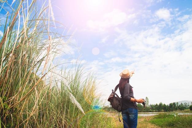 Femme heureuse voyageur à la recherche de ciel bleu avec champ de graminées, concept de voyage wanderlust, espace pour le texte Photo gratuit