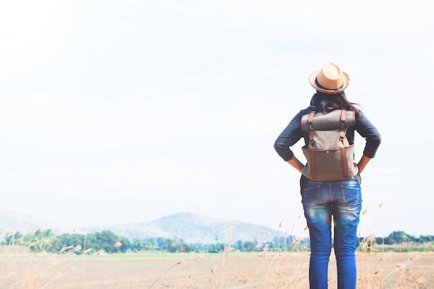 Femme heureuse voyageur à la recherche de ciel bleu avec fond de montagne, concept de voyage wanderlust, espace pour le texte Photo gratuit