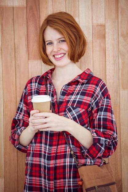 Femme hipster souriante tenant une tasse de café Photo Premium