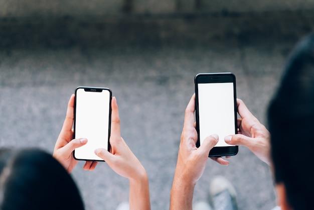 Femme et homme tenant un smartphone, maquette d'écran vide. en utilisant un téléphone portable sur lifestyl Photo Premium