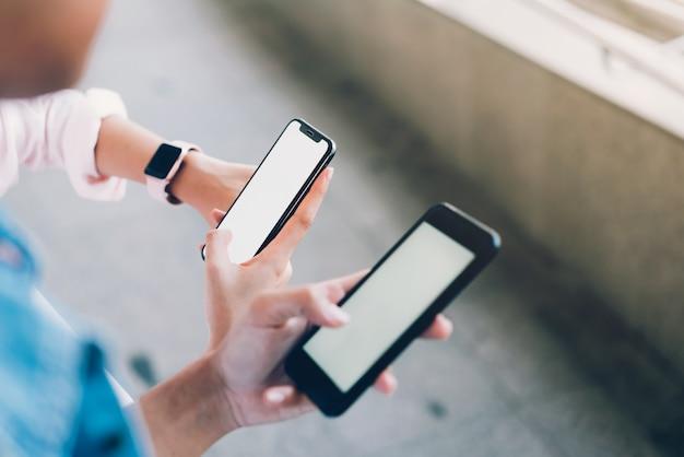 Femme et homme tenant un smartphone, maquette d'écran vide. en utilisant un téléphone portable sur le style de vie. Photo Premium