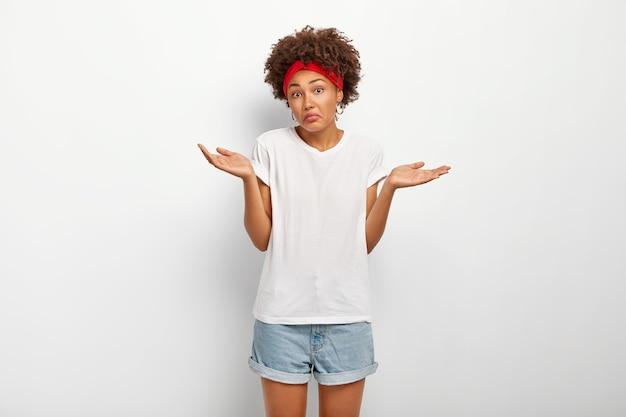 Femme Incertaine Et Désemparée Avec Une Coiffure Afro, écarte Les Mains Avec Le Doute Photo gratuit