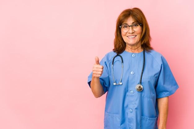 Femme D'infirmière Caucasienne D'âge Moyen Isolée Souriant Et Levant Le Pouce Photo Premium