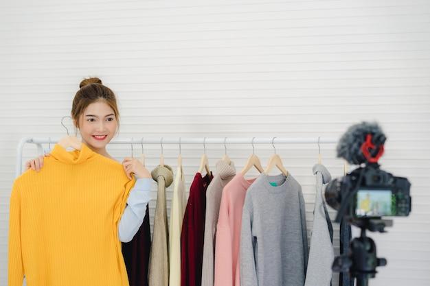 Femme influente en ligne de blogueuse mode asiatique tenant des sacs à provisions et beaucoup de vêtements Photo gratuit