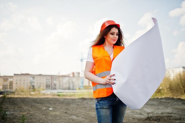 Femme ingénieur constructeur en gilet uniforme et casque de protection orange détiennent des documents commerciaux contre les nouveaux bâtiments avec grue. Photo Premium