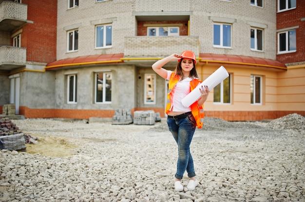 Femme ingénieur constructeur en uniforme gilet et casque de protection orange détiennent des documents commerciaux contre le nouveau bâtiment Photo Premium