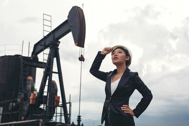 Femme ingénieure debout avec des pompes à huile de travail avec un ciel blanc. Photo gratuit