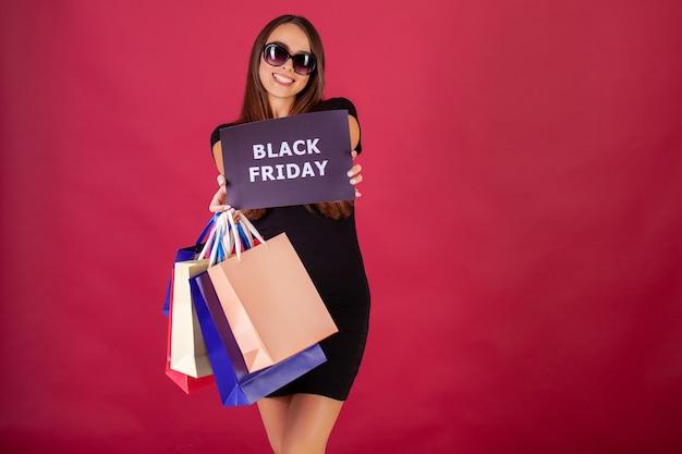 Femme avec inscription black friday et sacs à provisions Photo Premium