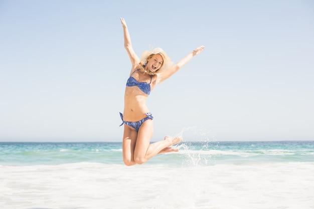 Femme insouciante en bikini sautant sur la plage Photo Premium