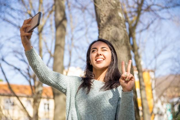 Femme insouciante grimaçant et prenant une photo de selfie à l'extérieur Photo gratuit