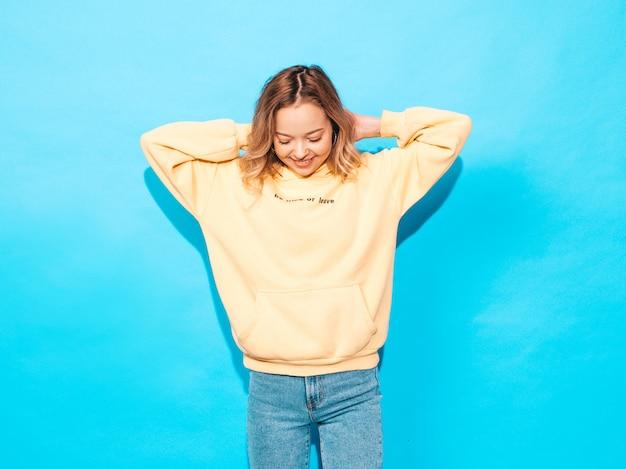 Femme Insouciante Posant Près Du Mur Bleu En Studio. Modèle Positif S'amusant Photo gratuit