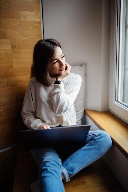 Une Femme Intéressée Travaille Sur Un Ordinateur Portable Tout En étant Assis Sur Une Large Fenêtre Dans La Journée Photo gratuit