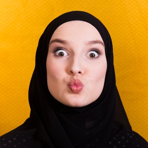 Femme islamique faisant la grimace contre une surface jaune Photo gratuit