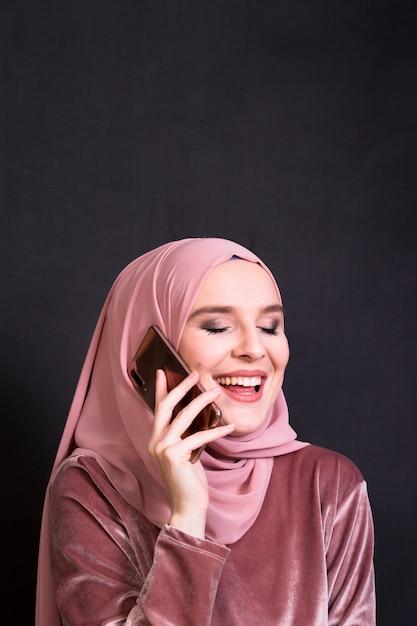 Femme islamique glamour rire tout en parlant au téléphone devant un fond noir Photo gratuit