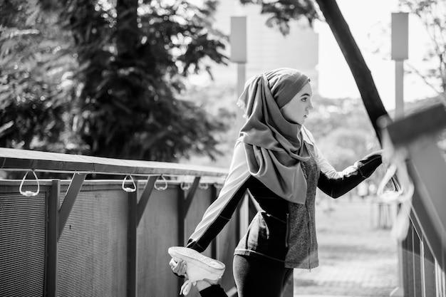 Femme islamique s'étendant après l'entraînement au parc Photo gratuit