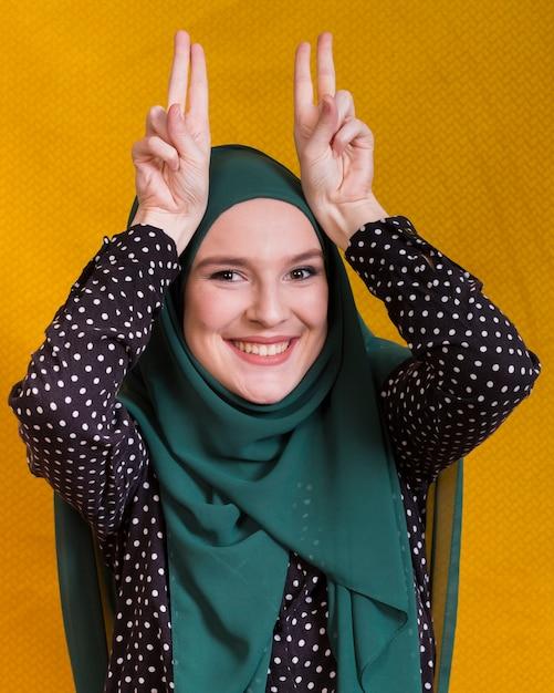 Femme islamique souriante faisant une grimace devant un fond jaune Photo gratuit