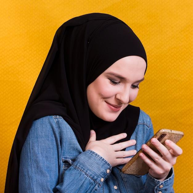 Femme islamique souriante avec foulard en regardant son téléphone portable Photo gratuit
