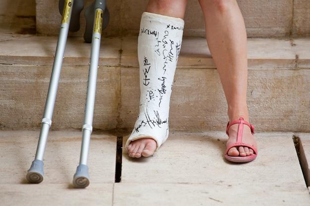 Une femme avec une jambe en plâtre et des béquilles Photo Premium
