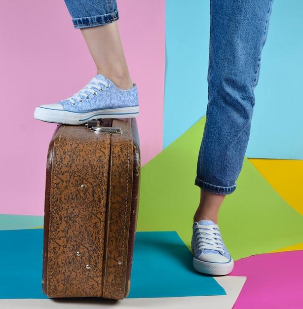 Femme Avec Un Jean Et Des Baskets Devient Un Pied Sur Une Valise Rétro Sur Un Mur De Papier Multicolore Photo Premium