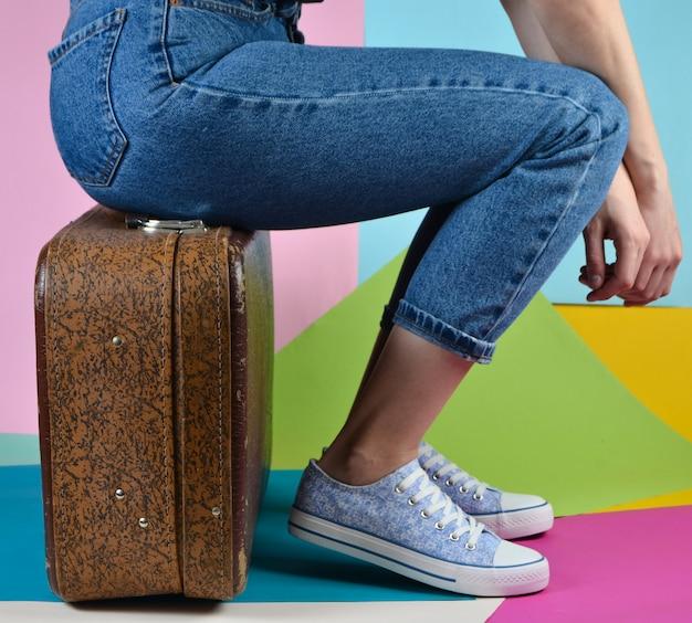 Femme Avec Un Jean Et Des Baskets Est Assis Sur Une Valise Rétro Sur Mur De Papier Multicolore Photo Premium