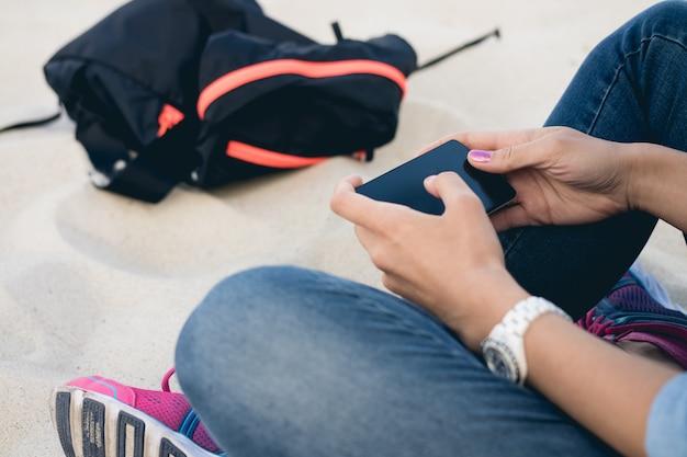 Femme, jean, séance, plage, sable, jambes croisées, utilisation, téléphone portable, écran tactile Photo Premium