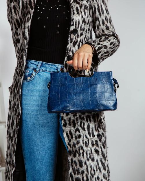 Femme en jean, top noir et cardigan imprimé léopard tenant un sac bleu marine Photo gratuit