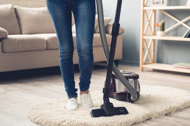 Femme en jeans à l'aide d'un aspirateur Photo Premium