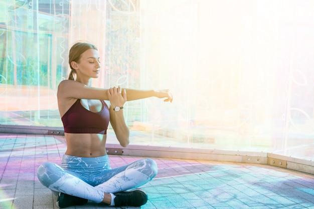 Femme jeune en bonne santé dans les vêtements de sport qui s'étend de la main pendant un exercice sur le pont Photo gratuit