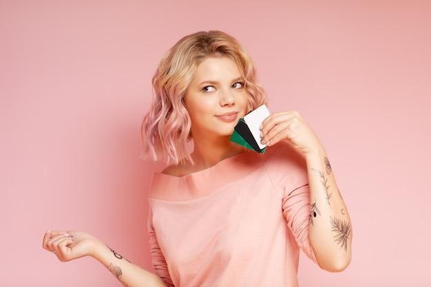 Femme jeune étudiant hipster avec cheveux colorés et tatouage détenant des cartes de crédit Photo Premium